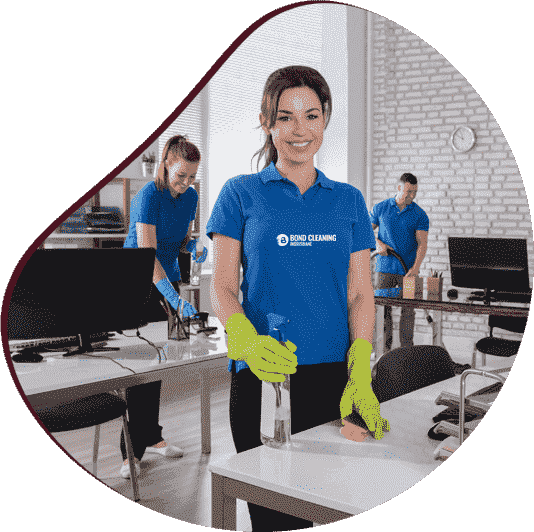 two woman in blue shirt wiping office table and man mopping the floor