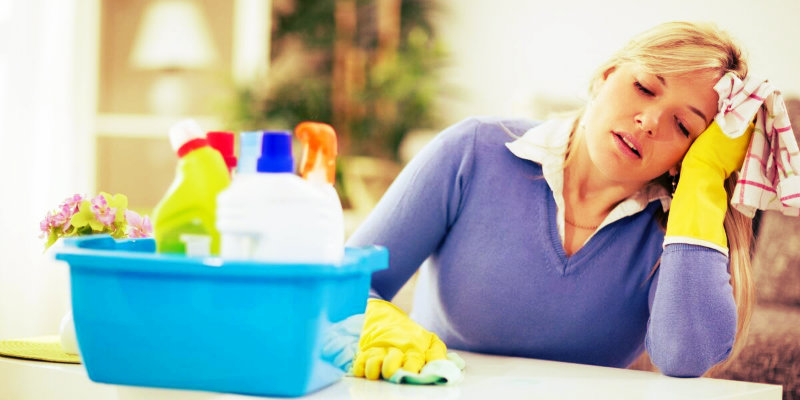tired woman in blue clothes holding rag in hand trying to dust the table
