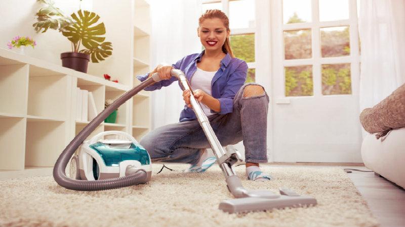 beautiful woman sitting and vacuuming the carpet