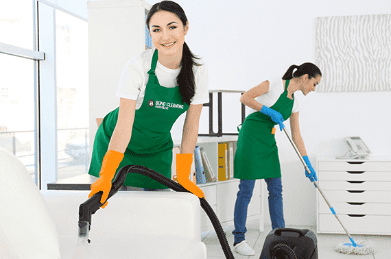 two young women vacuuming the couch and mopping the floor in an office