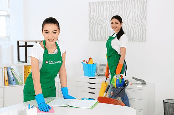 Young woman wiping office table and second one mopping the floor