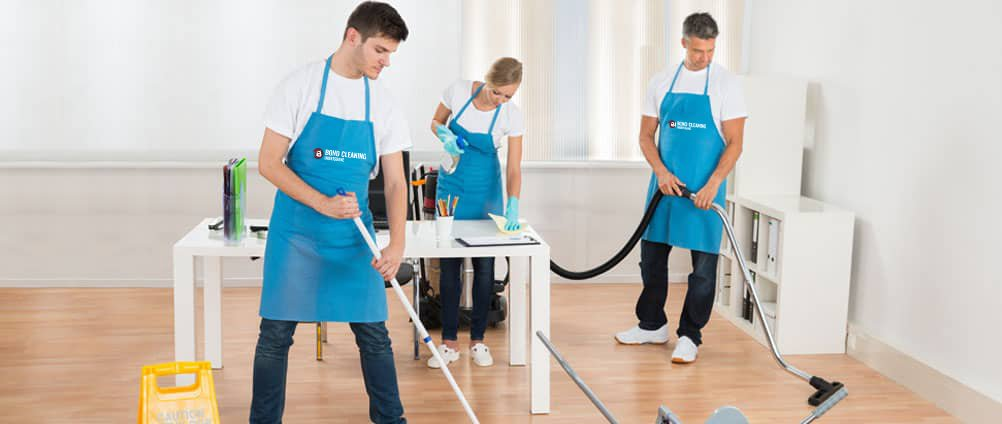 Two men mopping the floor and one woman wiping office table