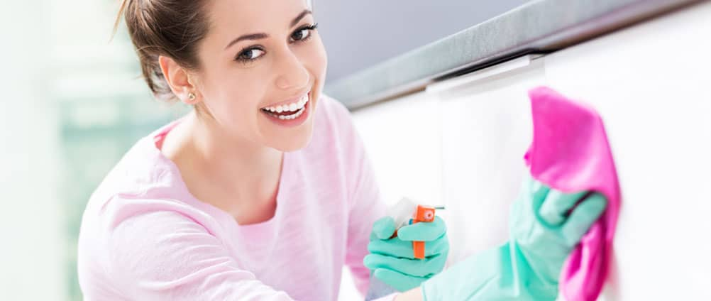 happy young woman wiping kitchen cabinet with rag