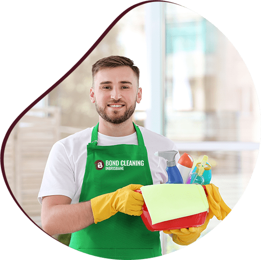 Male cleaner wearing green apron holding small bucket full of supplies