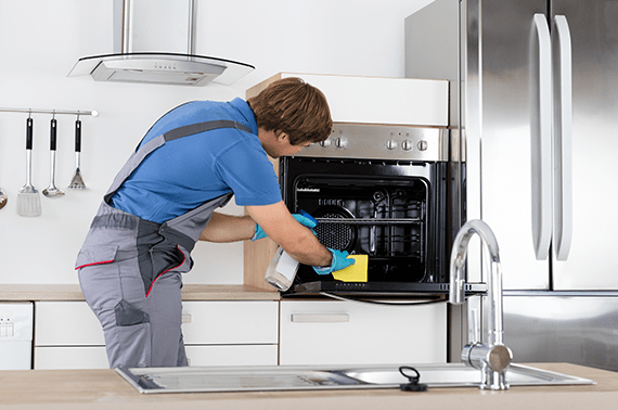 man in blue clothes wiping the oven and holding spray bottle in hand