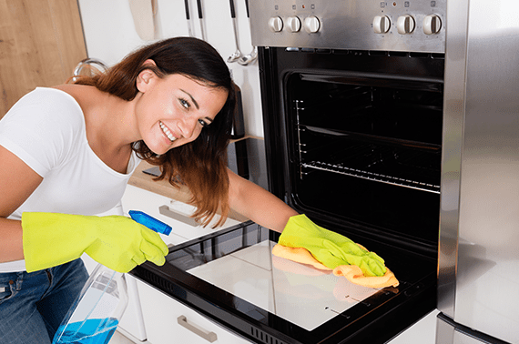 beautiful young woman sitting and wiping oven door wearing rubber gloves