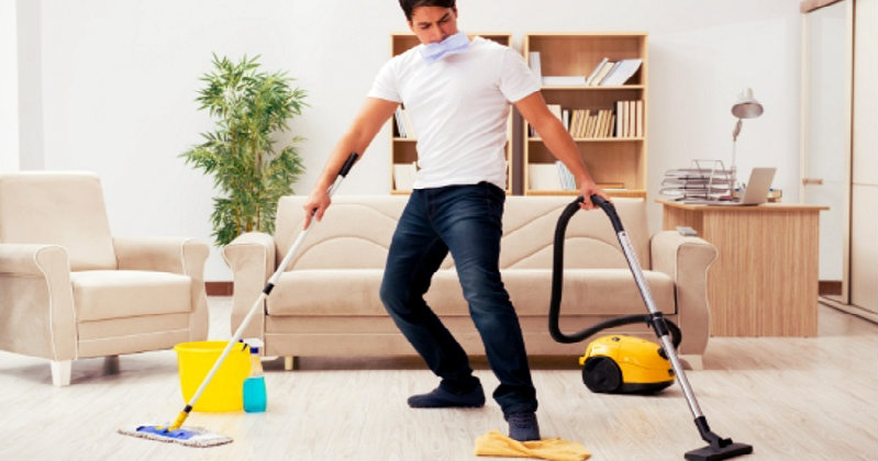 young man trying to mop and vacuum the floor simultaneously