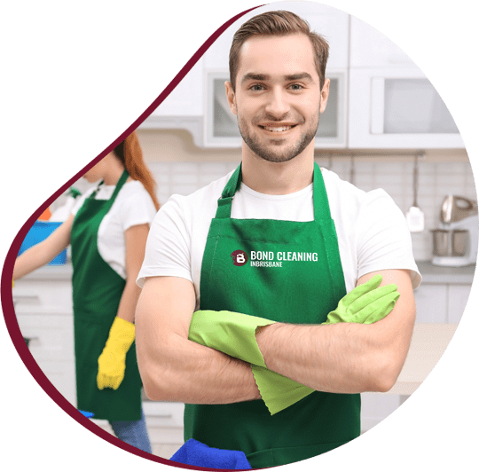 Male cleaner wearing green apron standing with folded hands and smiling