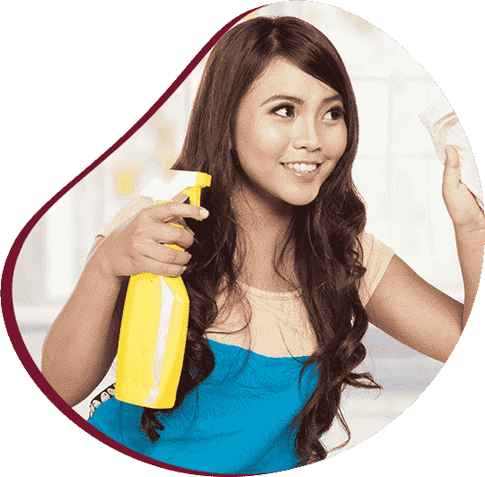beautiful young woman wiping kitchen surface and holding spray bottle in hand