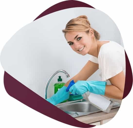 beautiful young woman wiping kitchen sink wearing protective gloves