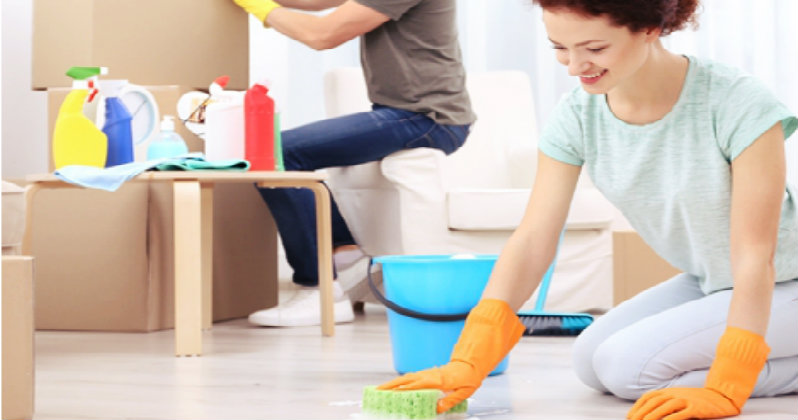 happy young woman wearing orange gloves scrubbing the floor