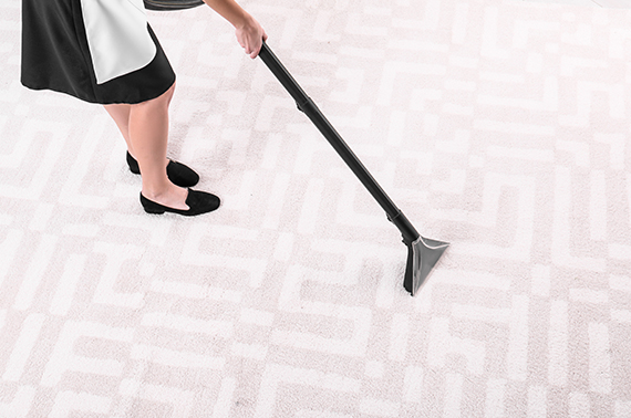 cropped image of young beautiful woman in black dress vacuuming the carpet
