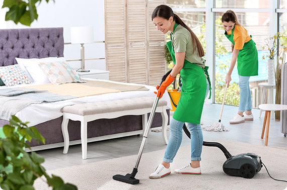 young beautiful woman in green apron vacuuming the carpet and one woman mopping the floor
