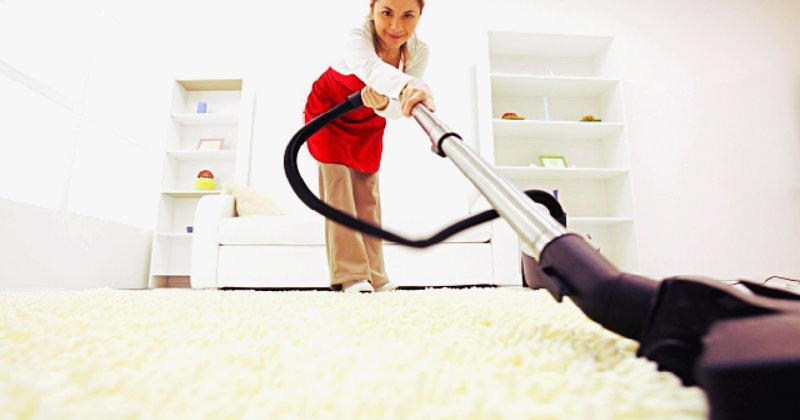 beautiful woman vacuuming the carpet