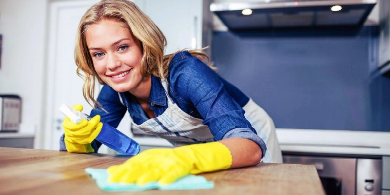 happy woman in blue shirt wiping kitchen counter