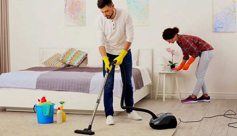 happy couple wiping and vacuuming bedroom