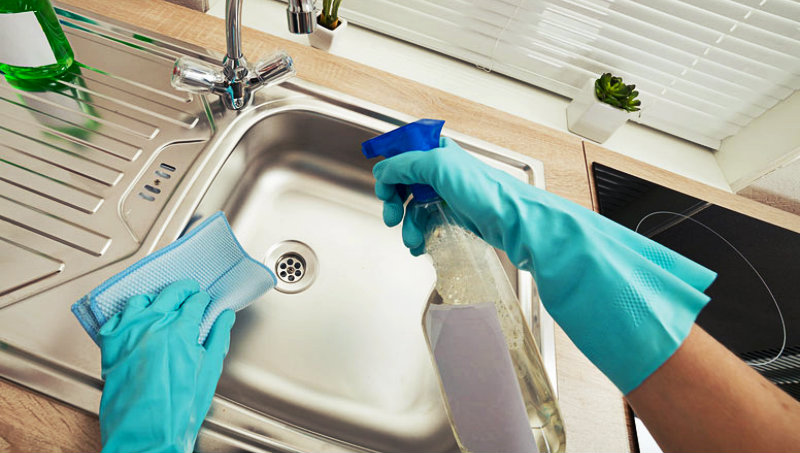 cropped image of a woman disinfecting kitchen sink