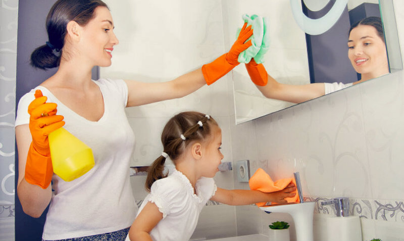 mother and daughter wiping mirror and basin in bathroom