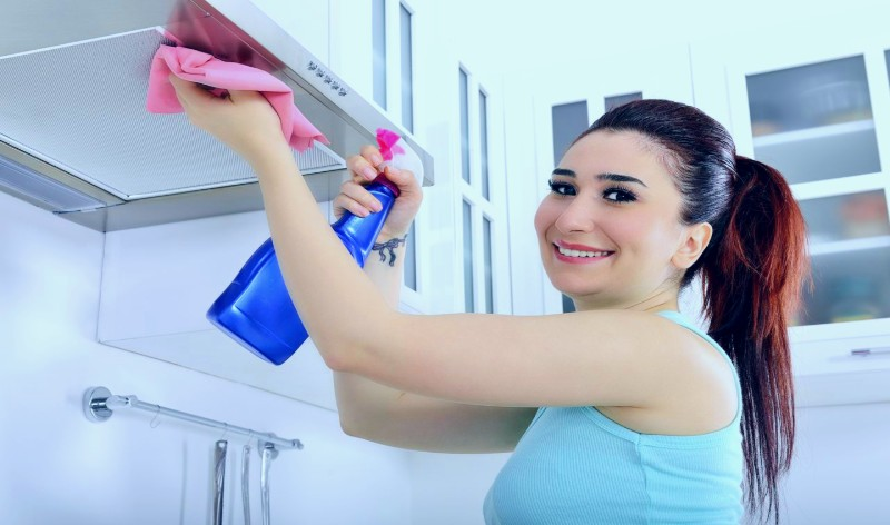 a woman dusting windows with dusting cloth in hand