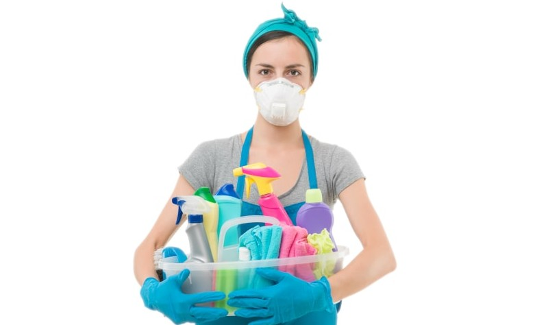 A woman is standing with a basket full of cleaning supplies