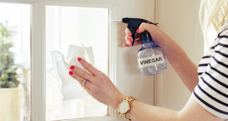 Woman disinfecting window glass with white vinegar and moping it with a cloth mop