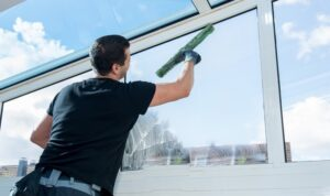 young man wiping window glass with a wiper