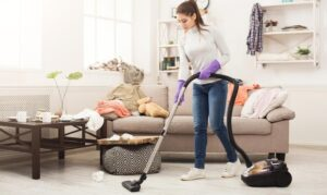 young woman vacuuming the floo