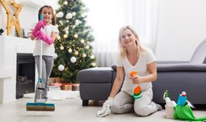 Young woman preparing her house for Christmas party with her daughter