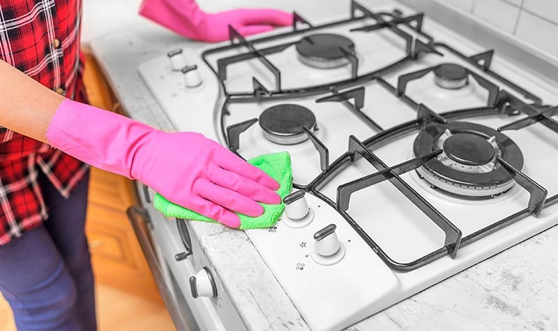 cropped picture of a woman wiping the gas stove