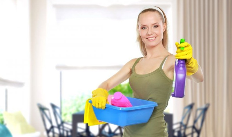 Young woman holding a bucket full of spray bottles and cloth wipes