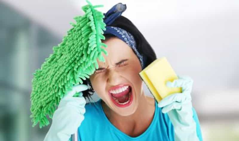 angry woman holding a sponge and a cloth mop in her hands