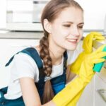 Young woman wiping a kitchen surface with a sponge