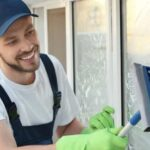 young professional wiping a sprucing a window glass